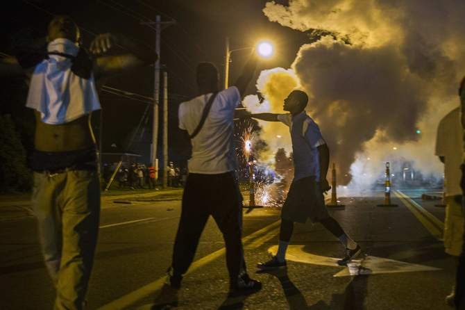 Protesters involved with a more vocal and confrontational group of demonstrators stand and gesture as tear gas is fired, at further protests in reaction to the shooting of Michael Brown near Ferguson, Missouri August 18, 2014. Photo: Reuters
