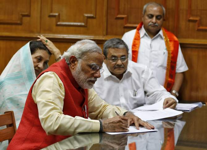 Hindu nationalist Narendra Modi, prime ministerial candidate for India's main opposition Bharatiya Janata Party (BJP), signs his nomination papers for the general elections in Vadodara, in the western Indian state of Gujarat April 9, 2014. Photo: Reuters