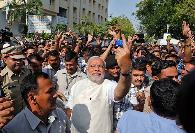 Hindu nationalist Narendra Modi (C), the prime ministerial candidate for India's main opposition Bharatiya Janata Party (BJP), shows his ink-marked finger to his supporters after casting his vote at a polling station during the seventh phase of India's general election in the western Indian city of Ahmedabad on Wednesday. Photo: Reuters