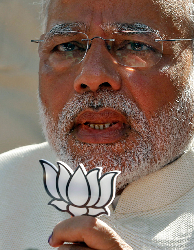 This reuters photo taken on April 30 shows Hindu nationalist Narendra Modi, the prime ministerial candidate for India's main opposition Bharatiya Janata Party (BJP), holds a lotus cut-out after casting his vote at a polling station during the seventh phase of India's general election in the western Indian city of Ahmedabad.