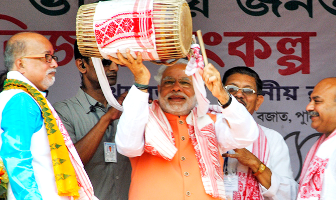 Hindu nationalist Narendra Modi (C), the prime ministerial candidate for India's main opposition Bharatiya Janata Party (BJP), plays a dhol, an Indian musical instrument, during an election campaign rally in Mangaldoi in the northeastern Indian state of Assam April 19, 2014. Photo: Reuters