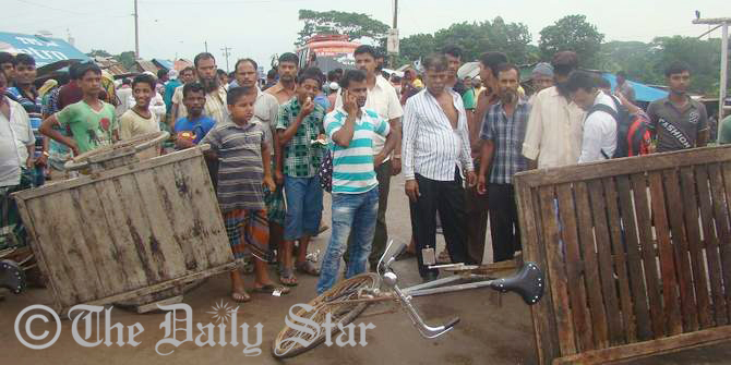 Relatives of missing launch capsize victims block a road in front of Padma Rest House near the Mawa ghat in Lauhajang upazila of Munshiganj for an hour Tuesday morning. At least 120 people went missing as the launch sank in the Padma river Monday. Photo: STAR