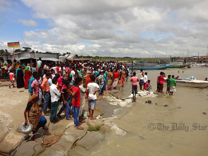 Hundreds of local people anxiously wait on the bank of river Padma as divers search for bodies of passengers of a launch that capsized in the river in Lauhajang upazila of Munshiganj on Monday. Photo: Star