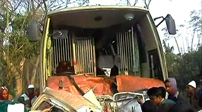 Locals crowd around the wreckage of a bus which rammed into a human hauler killing four people and injuring six in Sadar upazila of Natore this morning. Photo: TV grab