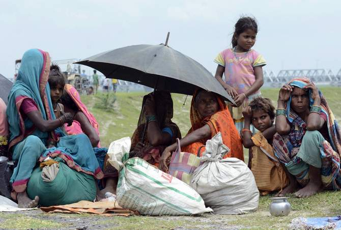 Villagers with their belongings sit in a relief camp after their evacuation at Supaul district in the eastern Indian state of Bihar August 3, 2014. Photo: Reuters