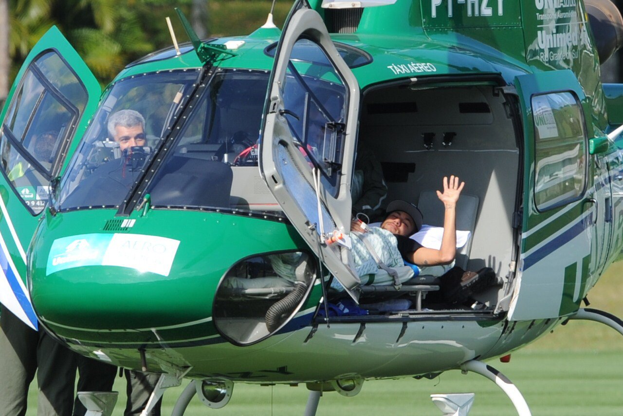 Brazilian striker Neymar waves on July 5, 2014 from inside the helicopter that will transport him from Teresopolis, Rio de Janeiro State, Brazil to his residence in Guaruya. Injured Brazil star Neymar departed his team's training base in Terespolis in a helicopter on Saturday and headed home to Sao Paulo, after his World Cup ended in agony on Friday night. Photo: AFP/ Getty Images