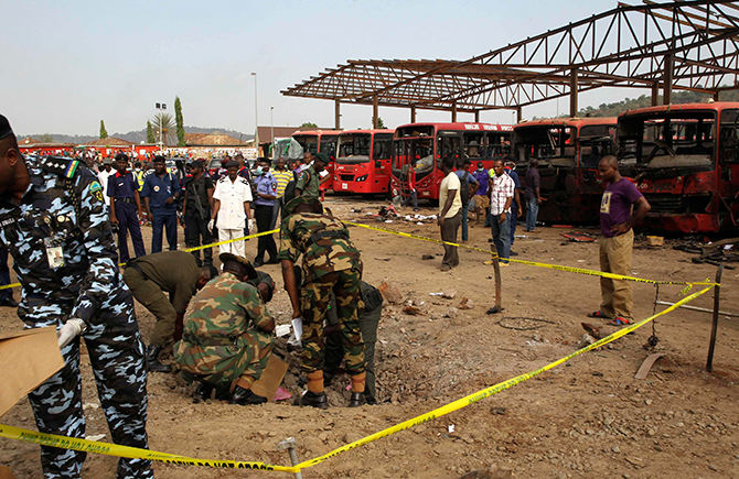 Bomb experts gather evidence in a crater that was caused by a bomb explosion at Nyanyan killing at least 71 people in Abuja of Nigeria on Monday. Photo: Reuters