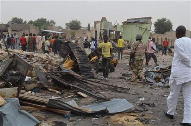 People gather at the site of a twin car bomb explosion in Maiduguri, Nigeria, March 2, 2014. Photo: AP/File