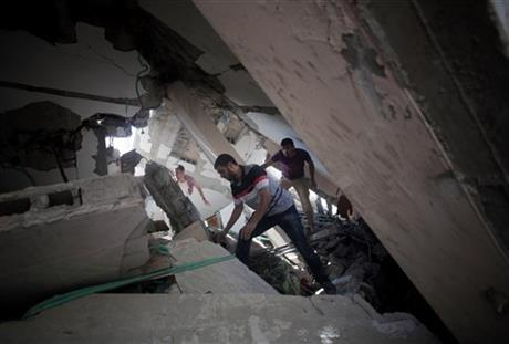 Palestinians search for survivors under the rubble of a house was destroyed by an Israeli missile strike, in Gaza City, Monday. Photo: AP