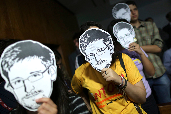 This Reuters photo taken on August 6, 2013 shows people wearing masks with pictures of former NSA contractor Edward Snowden during the testimonial of Glenn Greenwald, the American journalist who first published the documents leaked by Snowden, before a Brazilian Congressional committee on NSA's surveillance programs, in Brasilia.