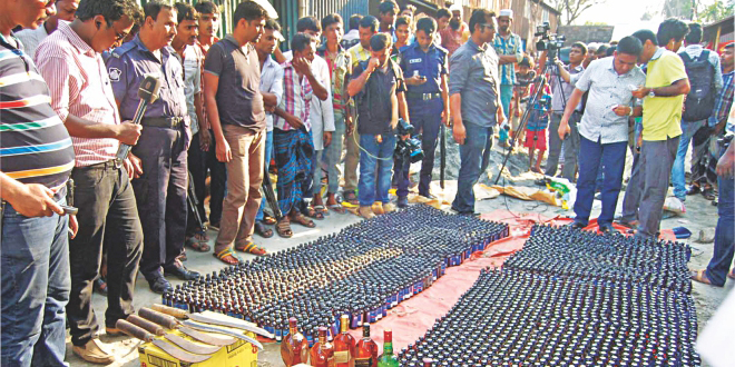 This Star photo taken on May 9 shows policemen displaying seized Phensedyl, foreign liquor and sharp weapons raiding Shimrail Truck Stand in Narayanganj. The contraband substances were recovered from the shops of Nur Hossain, prime accused in the Narayanganj seven-murder case.