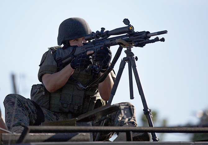 A riot police officer aims his weapon while demonstrators protest the shooting death of teenager Michael Brown, in Ferguson, Missouri in this file photo taken August 13, 2014.  U.S. President Barack Obama has ordered a review of the distribution of military hardware to state and local police out of concern at how such equipment has been used during racial unrest in Ferguson, Missouri. Photo: Reuters