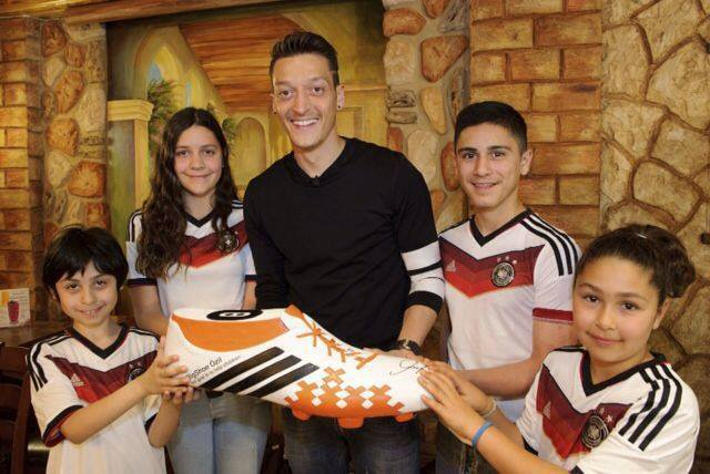 Ozil added a picture on his official Facebook profile showing him with four children holding a large football boot and kitted out in the Germany strip on Wednesday.