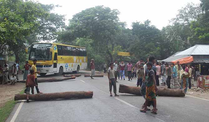 A bus took turns back as Awami League supporters and local people blockade a road felling tree logs Sunday morning in Dharmagram area of Pabna in protest of killing four Awami League men. Photo: Star
