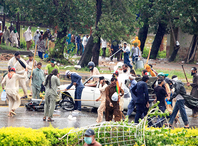 Anti-government protesters use sticks to hit a car and a motorcycle as they protest during Revolution March towards the prime minister's house in Islamabad September 1, 2014. Photo: Reuters