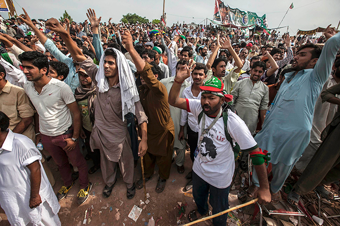 Supporters of Imran Khan, the Chairman of the Pakistan Tehreek-e-Insaf (PTI) political party, react as they listen to their leader in front of the Parliament house building during the Revolution March in Islamabad August 28, 2014. Photo: Reuters