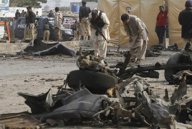 Security officials collect evidence at the site of an explosion in Karachi Thursday. An explosion targeting a bus full of Pakistani policemen killed 11 and injured 33 near the southern port city of Karachi.