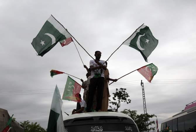 Supporters of Pakistan Tehreek-e-Insaf, a political party led by cricketer-turned-opposition politician Imran Khan, wave flags from the roof of a van as they arrive with the Freedom March in Islamabad August 16, 2014. Photo: Reuters