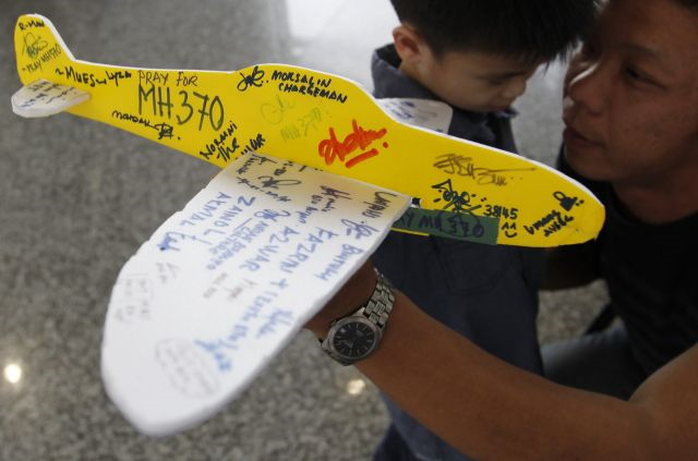 A man holds a model plane with well-wishing messages for the passengers of the missing Malaysian Airline plane at Kuala Lumpur International Airport, Malaysia, 15 March 2014. Photo: The Star
