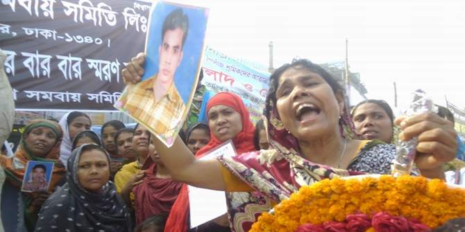 Mother of a Rana Plaza victim holds her son's photograph in her hand as she carries a wreath to place it at a monument in Savar erected in commemoration of all those people who lost their lives. She did not find her son's body since then. Photo: Star