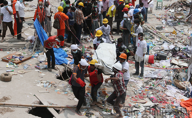 Volunteers bring out a body from the rubble of Rana Plaza after cutting a hole on the rooftop of the collapsed building. Photo: Star
