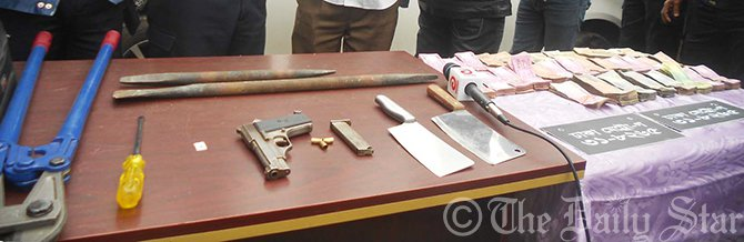 Law enforcers produce a pistol, 10 sharp weapons, looted money, a private car (not seen in the photo) and other equipment used to break locks before reporters after they were seized from the procession of a robber gang in Mithapukur upazila of Rangpur.