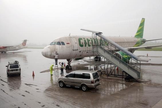 Workers stand near a Citilink airplane covered with ash from Mount Kelud at Adi Sucipto airport in Yogyakarta February 14, 2014. Photo: Reuters