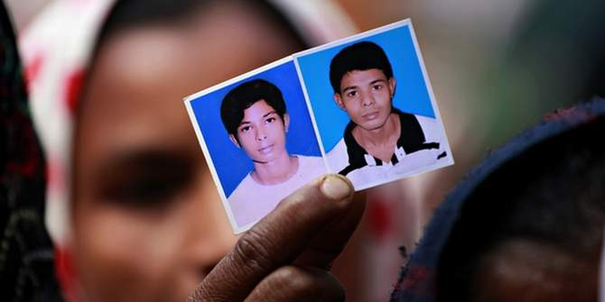 Relatives of victims killed in the Rana Plaza factory collapse hold their pictures. Photo: The Guardian