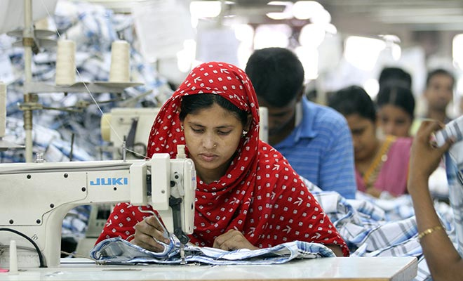 This Star file photo taken recently shows a female garment worker is busy threading clothes at a factory in Gazipur, Bangladesh.