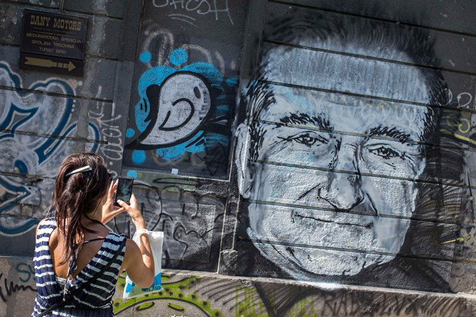 A woman takes a picture of a mural depicting late actor Robin Williams in Belgrade, August 13, 2014. The mural was drawn on a building in downtown Belgrade by an unknown artist on Tuesday. Photo: Reuters