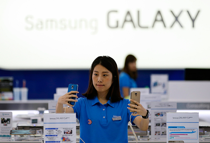 A sales assistant checks Samsung Electronics' Galaxy S5 smartphones at a shop in Seoul July 29, 2014. Photo: Reuters