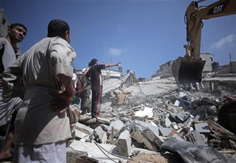 Palestinian rescuers search for bodies and survivors in the rubble of homes which were destroyed by an Israeli missile strike, in Gaza City, Monday. Photo: AP