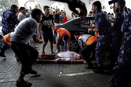 Palestinian medics carry a wounded woman to an emergency room at Shifa hospital in Gaza City, Sunday. Photo: AP