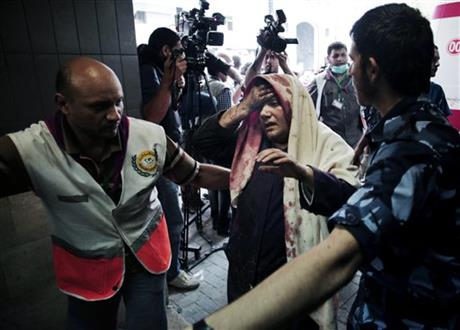 Palestinians escort a wounded woman to the emergency room of Shifa hospital in Gaza City, northern Gaza Strip, Sunday. Photo: AP
