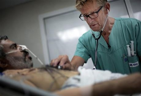 In this Wednesday, July, 16, 2014, Mads Gilbert, Norwegian doctor who has volunteered at Shifa on and off for 17 years, treats a man at the emergency room of the Shifa hospital in Gaza City. Photo: AP