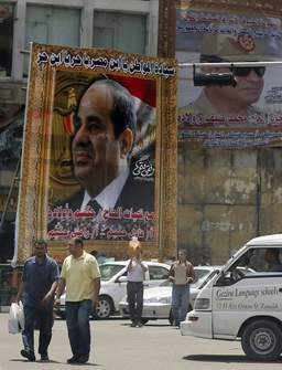 People walk near huge banners for Egypt's former army chief Field Marshal Abdel Fattah al-Sisi in downtown Cairo April 28, 2014. Photo: Reuters