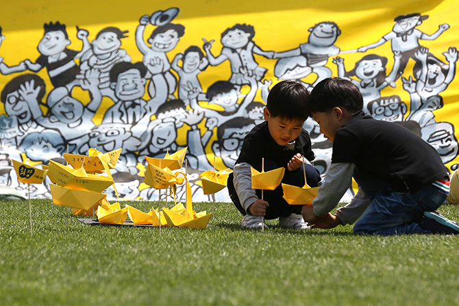 Children play with yellow coloured paper ships near a memorial altar for victims onboard passenger ship Sewol set up at Seoul City Hall Plaza on Sunday. A culture of cosy personal ties that can blur the lines between businesses and those regulating them, of profit over safety, and soft courts is in focus as South Korea demands answers over the sinking of a ferry with the loss of more than 300 lives, mainly high school students. Photo: Reuters