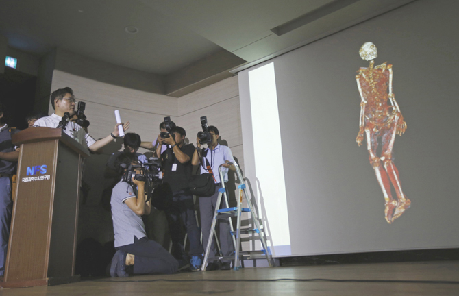 Seo Joong-seok (L), director general of South Korea's National Forensic Service (NFS), gives a briefing on the cause of death of businessman Yoo Byung-un, as a 3D scanned image of Yoo's body is projected on a screen at the agency office in Seoul July 25, 2014. Photo: Reuters