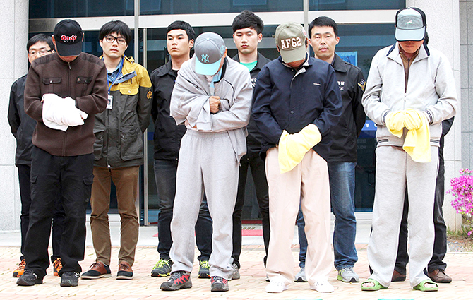 Crew members (front row) of the sunken Sewol ferry stand outside a court in Mokpo, after investigators sought for warrants of their arrest at the court April 26, 2014. Photo: Reuters
