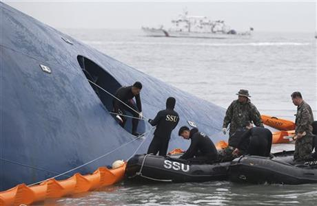 In this April 17, 2014 file photo, South Korean rescue team members try to rescue passengers trapped in the ferry Sewol sinking in the water off South Korea's southern coast near Jindo. Photo: AP