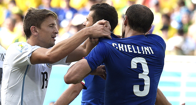 Italy's defender Giorgio Chiellini (R) attempts to show a bite mark by Uruguay striker Luis Suarez as Uruguay midfielder Gaston Ramirez pulls his shirt up during a Group D football match between Italy and Uruguay at the Dunas Arena in Natal during the 2014 FIFA World Cup on June 24, 2014. Photo: AFP/Getty Images
