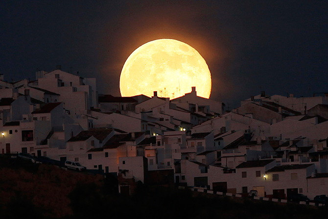 The Supermoon rises over houses in Olvera, in the southern Spanish province of Cadiz, July 12, 2014. Occurring when a full moon or new moon coincides with the closest approach the moon makes to the Earth, the Supermoon results in a larger-than-usual appearance of the lunar disk. Photo: Reuters