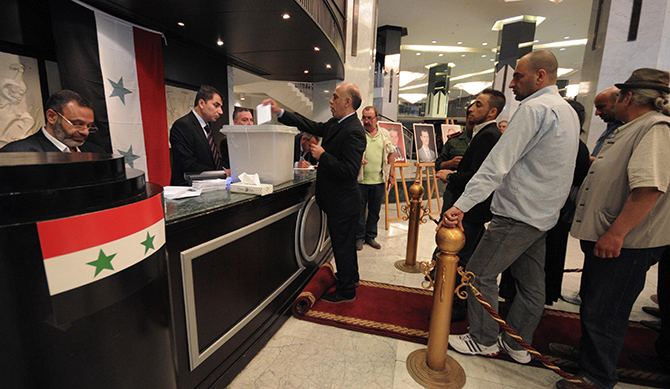 A man casts his vote as others wait for their turn at the Dama Rose hotel during the presidential election in Damascus, June 3, 2014. Photo: Reuters