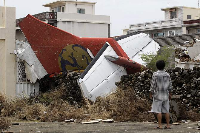 A man stands in his backyard and looks at the wreckage of a TransAsia Airways turboprop plane that crashed on Taiwan's offshore island Penghu July 24, 2014. The leaders of rivals China and Taiwan expressed condolences on Thursday for victims of the plane that crashed during a thunderstorm the previous day killing 48 people including two French nationals. Photo: Reuters