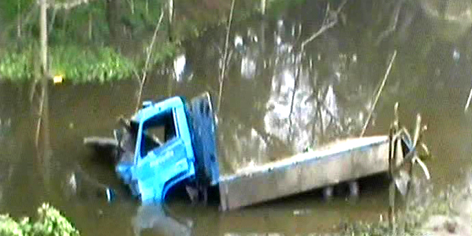 A damaged truck lies in a roadside ditch in Basail upazila of Tangail. The vehicles fell there after being hit by a Dhaka-bound train on Friday morning. Two persons were killed and 12 injured in the accident.