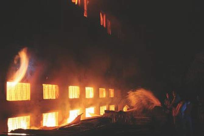 Locals try to douse the flames in Tazreen Fashion near Dhaka Export Processing Zone in Ashulia on November 24, 2012. The fire gutted several floors of the eight-storied factory and at least 113 workers were killed in the incident. Photo: STAR