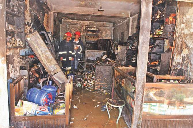 This April 11 photo shows firemen inspecting the devastated shop after the chemical explosion at Tejturi Bazar in the capital.