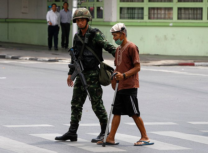 A Thai soldier helps an aged man cross a road outside the Army Club in Bangkok on Tuesday. Photo: Reuters