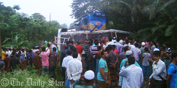 People crowd the accident site where 10 people including two children were killed as a train hit a bus carrying a wedding party while it was crossing the rail lines at Barobazar of Kaliganj upazila in Jhenidah early Friday. Photo Star