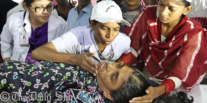 Doctors take care of a garment worker of Tuba Group who is on hunger strike with her colleagues inside the factory in Badda in the capital on Sunday. They have been on the strike since the day before Eid demanding unpaid wages of three months and Eid bonuses. Photo: Amran Hossain